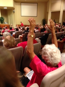 A woman raises her hands in agreement to something a speaker is saying about standardized testing.